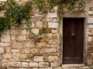 A stone wall and wooden door in Montefioralle, Italy