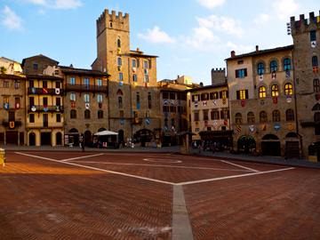 The golden rays of the setting sun wrap themselves over the buildings surrounding Piazza Grande in Arezzo, Italy