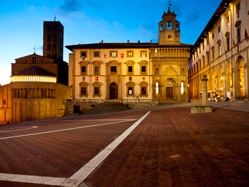 The buildings of Piazza Grande aglow at dusk in Arezzo, Italy
