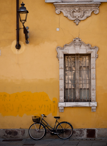 Ornate window, lantern and bicycle on a yellow wall in Parma, Italy