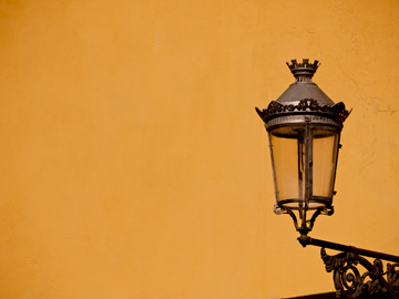 A wall lantern on a yellow wall in Parma, Italy