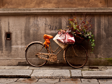 A bicycle is displayed outside of a clothing storm in Parma, Italy