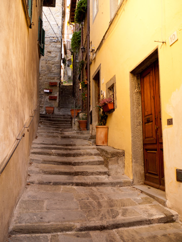 A small staired street climbs up in Cortona, Italy