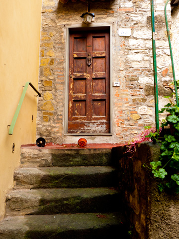 A wooden door on an old stone home in Tuscany