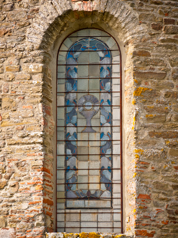 A thousand year old stained glass window in a Tuscan abbey.