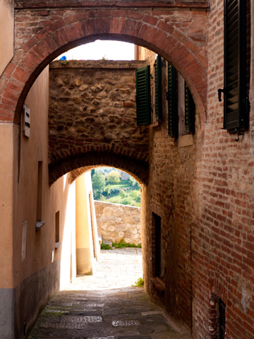 A street covered with stone and brick arches leads to the city walls of Montepulciano, Italy
