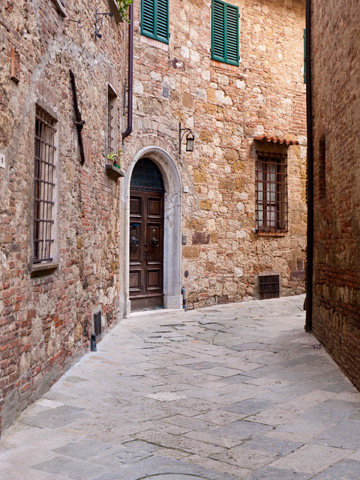 An old stone street bends around a corner in Montepulciano, Italy.