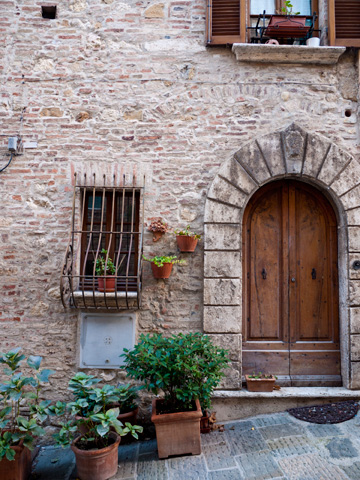 A medieval, stone building with a wooden door and potted plants in Montepulciano, Italy.