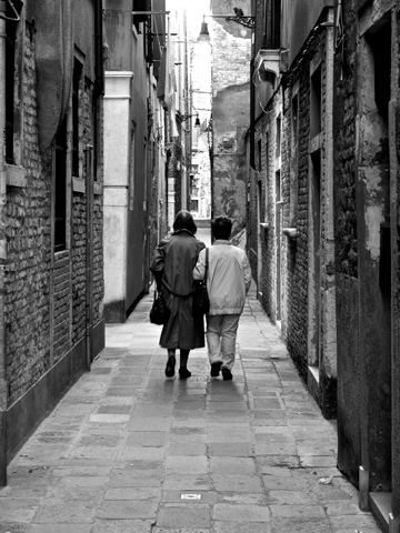 Two women walk arm in arm down a small street in Venice, Italy