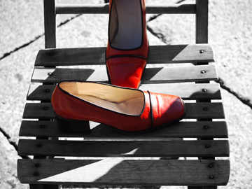 A pair of red shoes on a black and white, wooden chair