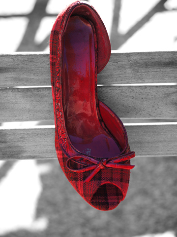 A plaid, red slipper shoe on a black and white background