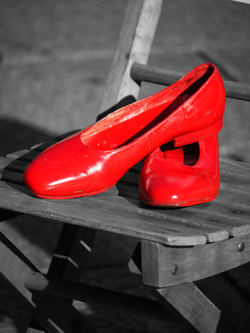 A bright red pair of shoes on a wooden chair.