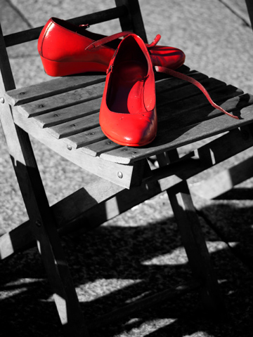 A pair of red shoes on a wooden chair