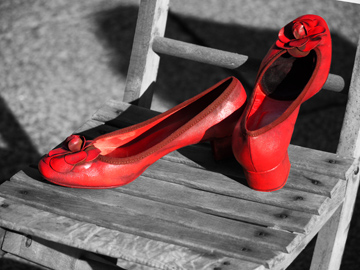 A pair of woman's red shoes on a wooden chair