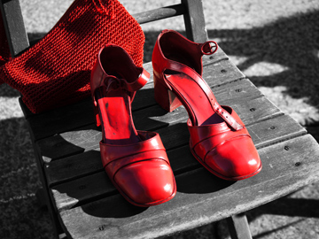 A pair of red shoes and handbag stand out on a black and white background