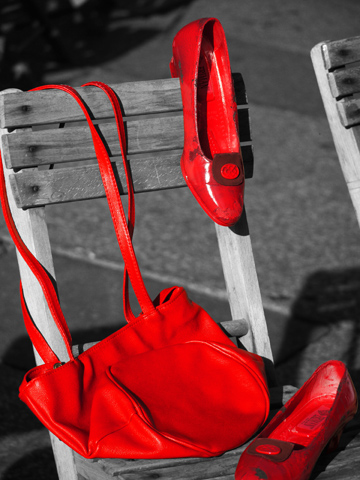 Red shoes and a red purse on a black and white background.
