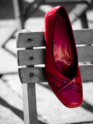 A red shoe on a wooden chair.