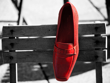 A red shoe on a black and white, wooden chair