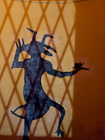 An illuminated devil is painted on a wall in Bologna, Italy