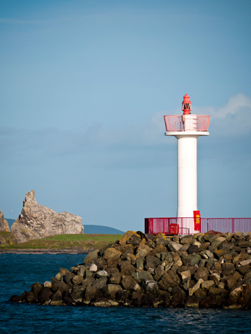 A lighthouse on rocky terrain in Howth, Ireland