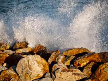 The spray of crashing waves on golden rocks.