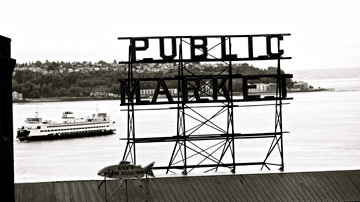 A Washington Ferry travels behind this Public Market sign at Pike Place Market in Seattle, USA
