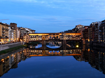The Ponte Vecchio and surrounding buildings are reflected in the Arno river at dusk