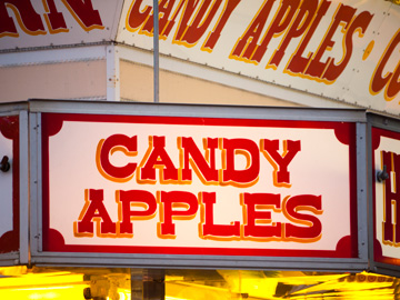 A neon sign over a candy apple kiosk at a carnival