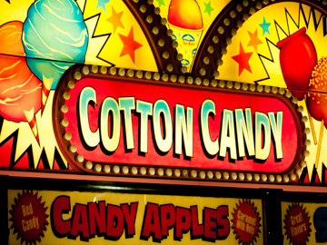 Cotton candy and candy apples advertised on a neon sign at a carnival