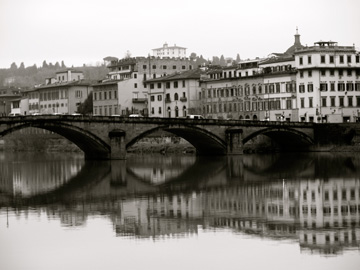 A bridge and buildings along the Arno River in Florence, Italy
