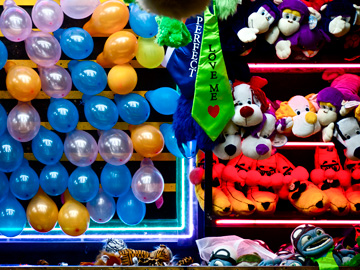 Carnival prizes displayed at a balloon popping game at a fair