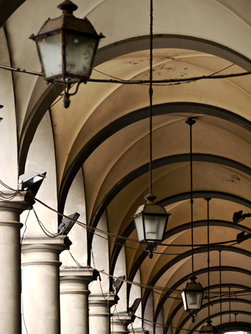 Lanterns hang down this arched walkway outside an apartment building in Florence, Italy