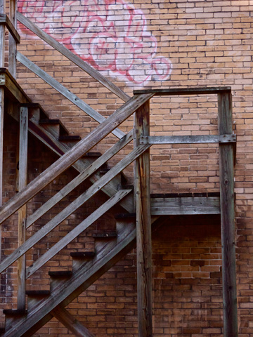 A wooden stairwell along a graffitti laden brick wall in Vancouver, British Columbia