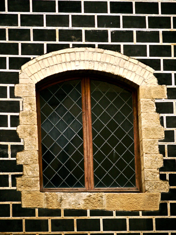 A laticed window set on a black brick wall