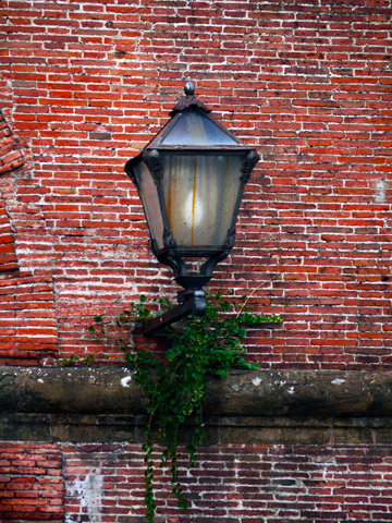 A lantern on a brick wall of the Fortezza in Florence, Italy