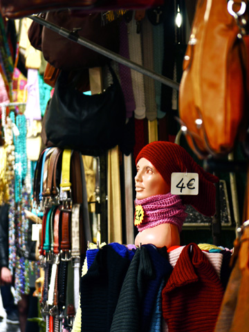 Scarves, belts and purses are on display in the streets outside of the San Lorenzo Market