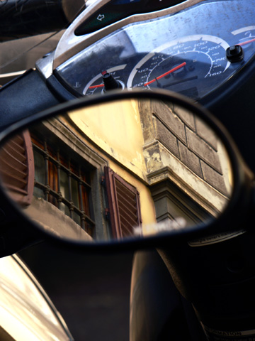 A window is reflected in the mirror of a moped
