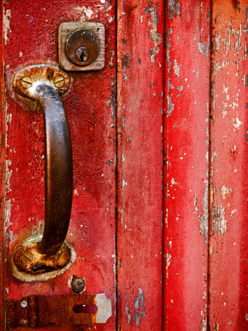 The rusted handle and lock on a red door