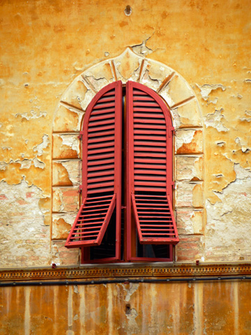 A building in Siena, Italy with a red shuttered window and peeling paint