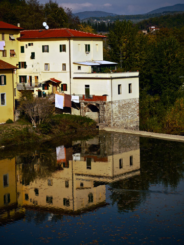 Apartment buildings reflected in the Arno river in Italy.