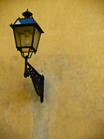 A lamp on a yellow wall in the Boboli Gardens in Florence, Italy